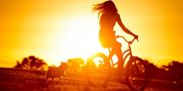 A silhouette of a young woman riding her bike with her dog running close behind.