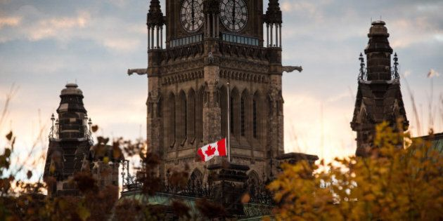 OTTAWA, ON - OCTOBER 23: A flag next to the Canadian Parliament Building is flown at half-staff one day...