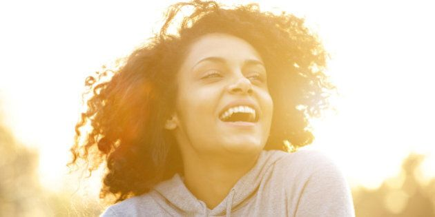 Close up portrait of a happy african american girl laughing outdoors