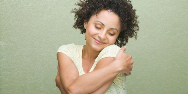 Pretty woman with curly hair hugging herself, on green background.