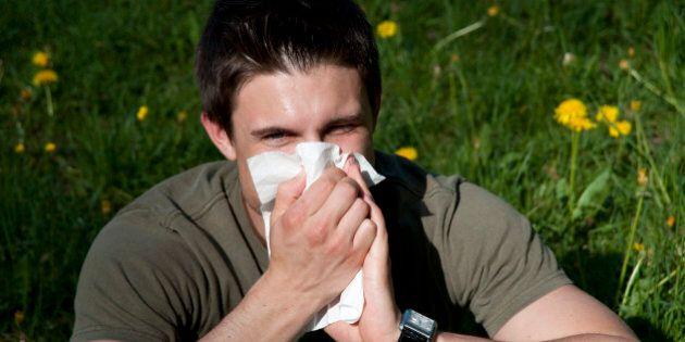 Man blowing nose in park, English Garden, Munich, Bavaria, Germany