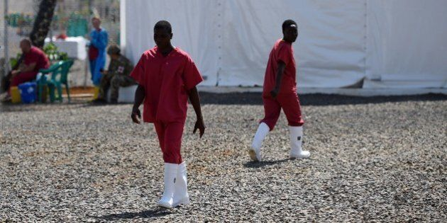 A photo taken on November 13, 2014, shows health workers walking at the Kerry Town Ebola treatment center...