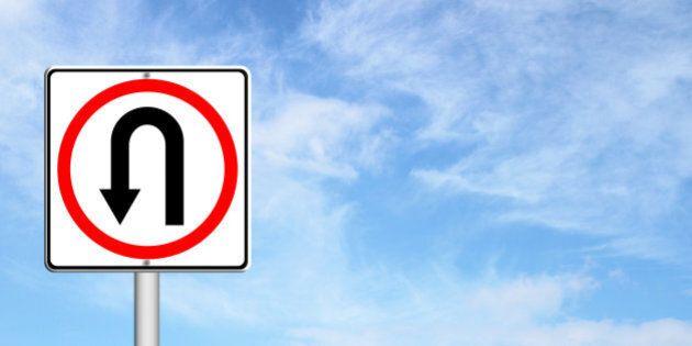 Turn back road sign over blue sky blank for