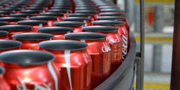 Empty Coca-Cola Classic cans move along a conveyor to be filled and sealed at a Coca-Cola Amatil Ltd....