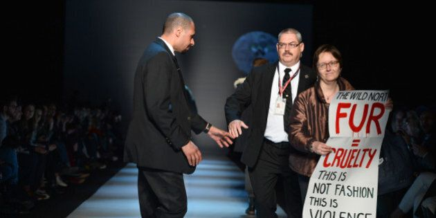TORONTO, ON - MARCH 27: Security escorts a protester holds an anti-fur off the runway during the show...