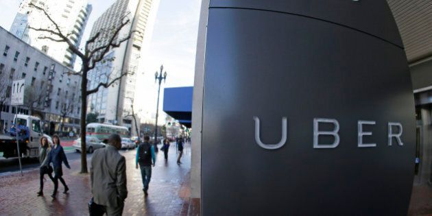 In this photo taken Tuesday, Dec. 16, 2014, people go past the headquarters of Uber in San Francisco....