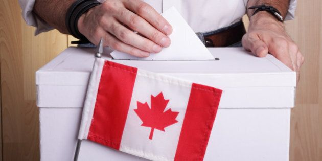 A man casting his vote. The Canadian flag is in front of the ballot