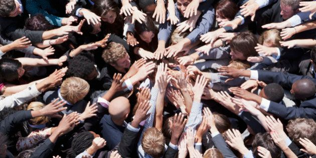 Crowd of business people extending hands in
