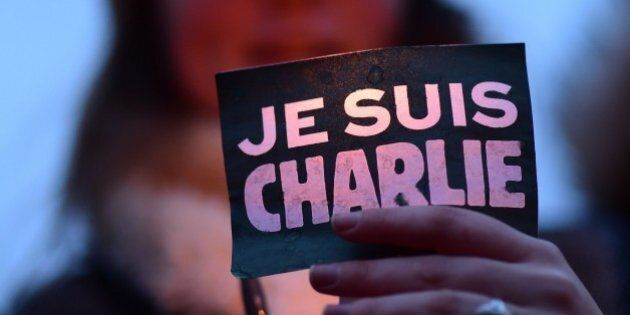 A woman holds a sign reading 'Je suis Charlie' (I am Charlie) during a gathering in Brussels on January...