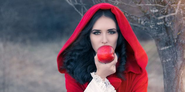 Fairytale image of a beautiful  girl wearing a red hood near the forest