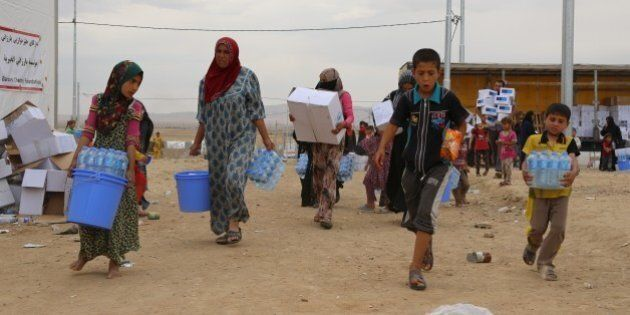 MOSUL, IRAQ - MAY 11: Refugees carry water and food aid distributed by charities after escaping from...