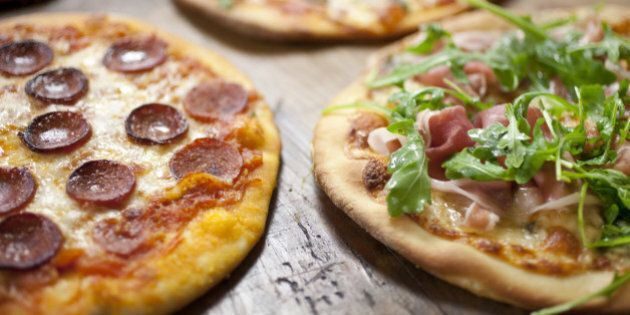 Mushroom, pepperoni, margherita, cheese and prosciutto pizzas on a large wooden cutting