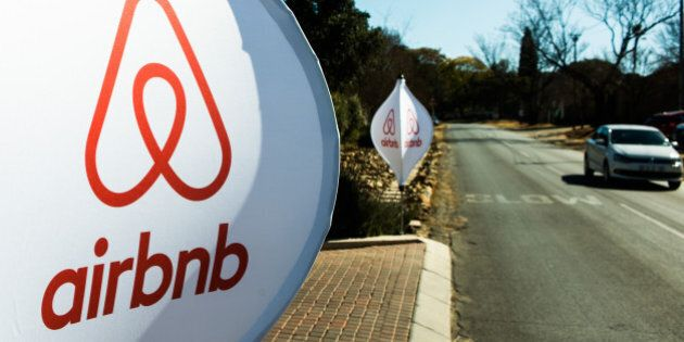 The logos of Airbnb Inc. sit on banners displayed outside a media event in Johannesburg, South Africa,...