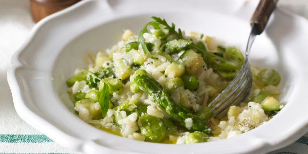Risotto primavera served in white bowl with fork on table, close-up