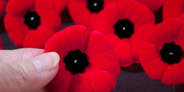 [UNVERIFIED CONTENT] The red poppy is a symbol of remembrance for all the men and women who fought in war.  This design is Canadian.  A hand is selecting a pin from many.