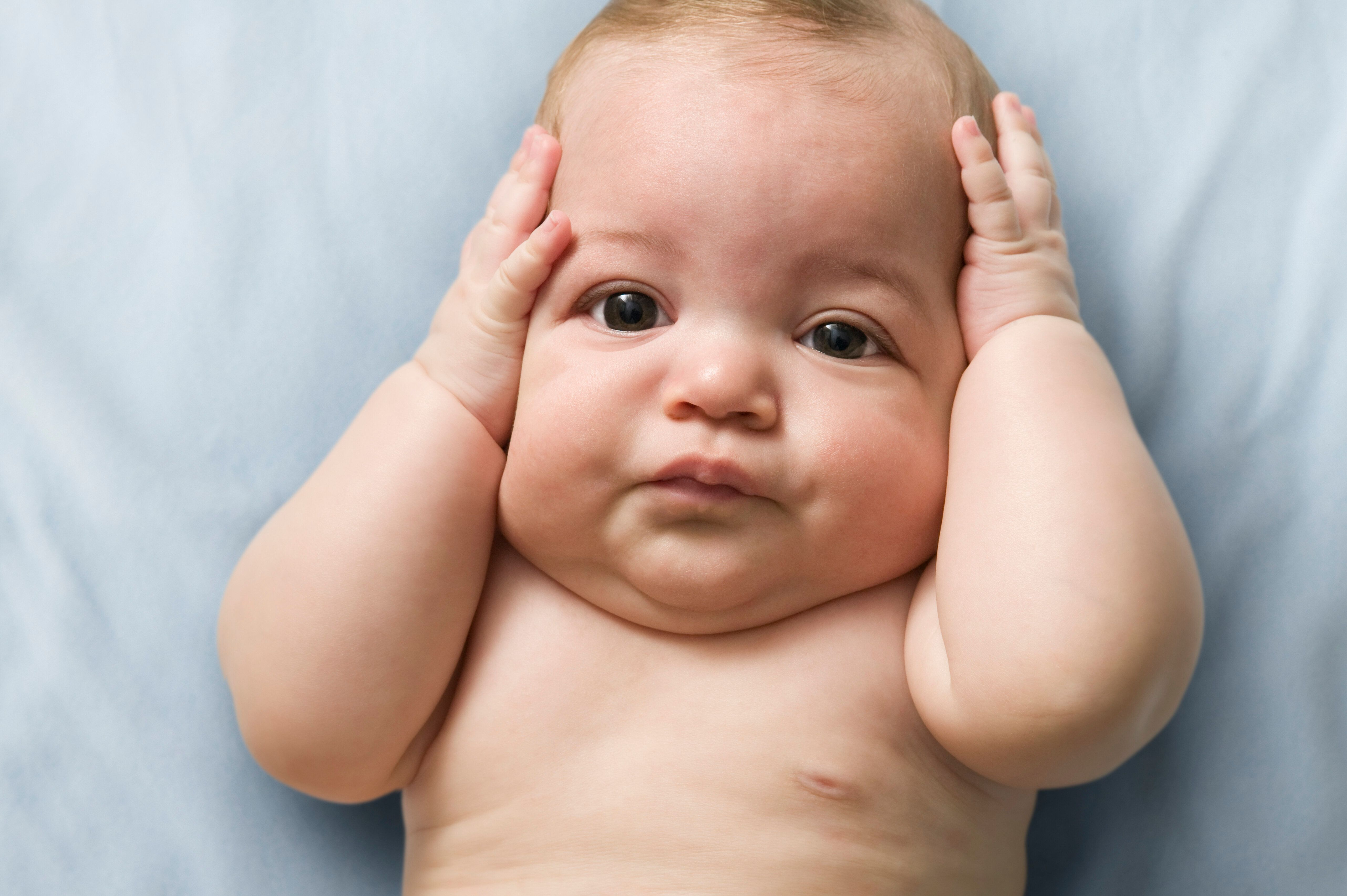 serious baby with hands in head