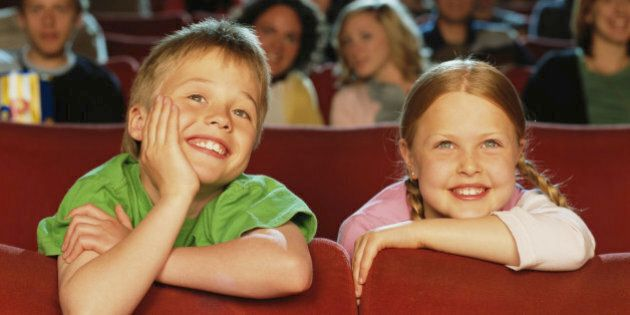 Boy and girl (8-10) in cinema, smiling,