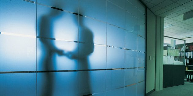 Silhouette of a Businessman Standing Behind a Frosted Glass Window in An Open Plan office Receiving a...