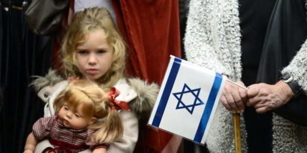 A young girl with her doll stands past a woman holding an Israeli flag and a Spanish flag during a rally...