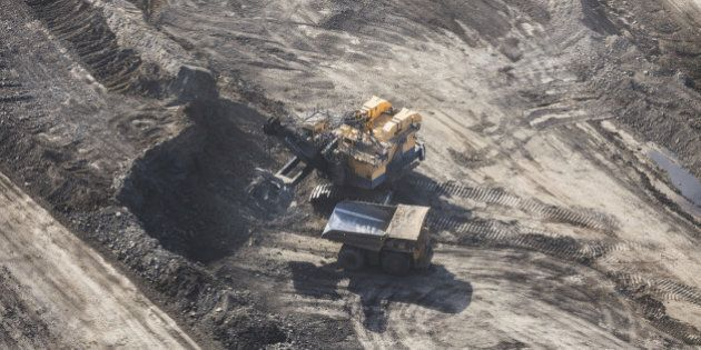 Aerial photo of a large power shovel excavating huge amounts of rock and sand into a dump truck.