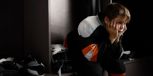 'Portrait of a male youth hockey player sitting in the dressing room tired, after the hockey game.Click...