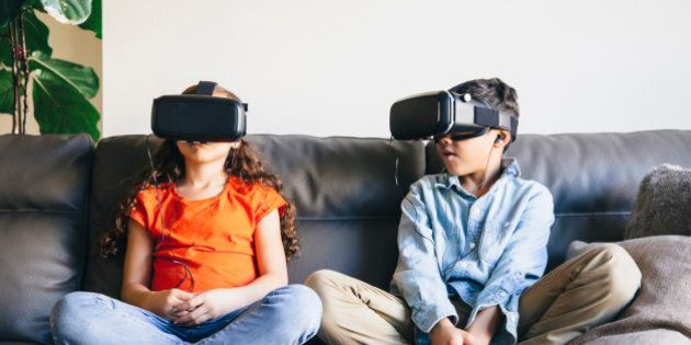 Mixed race children using virtual reality goggles on sofa