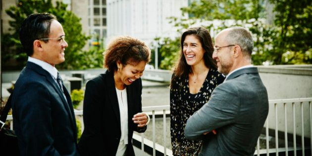 Four laughing business colleagues in discussion outside of office