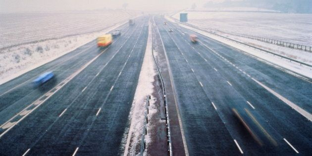 Motorway in winter, clear lanes surrounded by snow, elevated