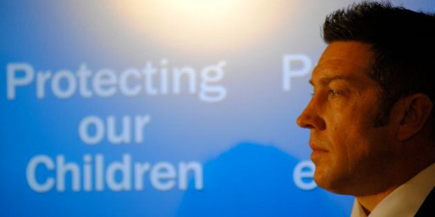 Former hockey player Sheldon Kennedy listens to the unveiling of new legislation to protect children...