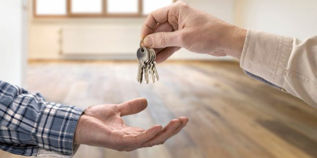 Realtor giving house key to buyer in empty room.