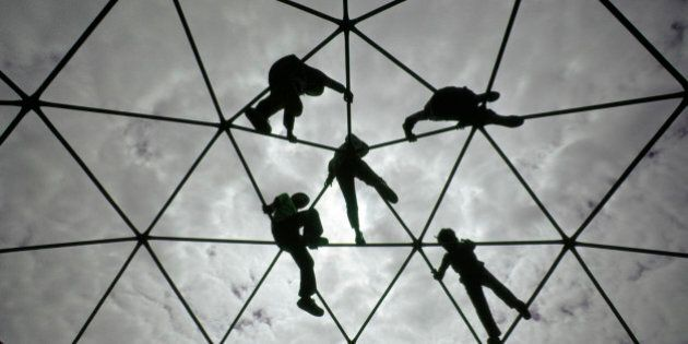 Ethnically diverse young boys and girls silhouetted against the sky while playing and climbing together...