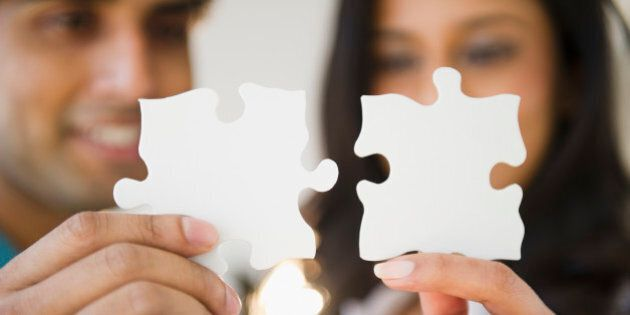 Mixed race couple holding puzzle pieces