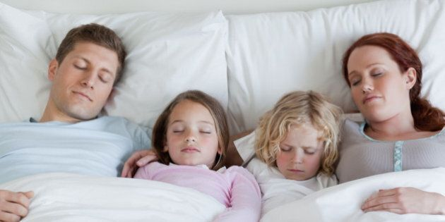 Adorable young family sleeping in the bed