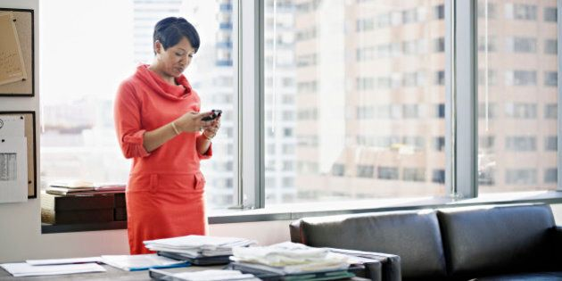 Businesswoman standing in office looking at smart phone