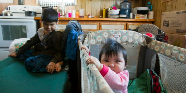 Ten-month-old Mylee stands in her crib as her brother sits on a temporary cot in their home in Attawapiskat,...