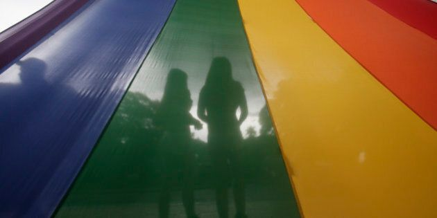 A LGBT (Lesbians Gays Bisexuals and Transgenders) couple is silhouetted by their rainbow-colored symbol...