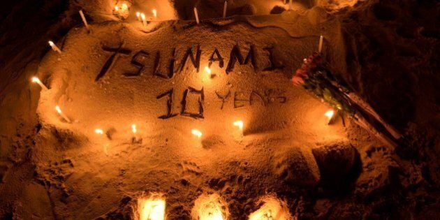 Candles on a sand sculpture are seen during commemorations on the the tenth anniversary of the 2004 tsunami...
