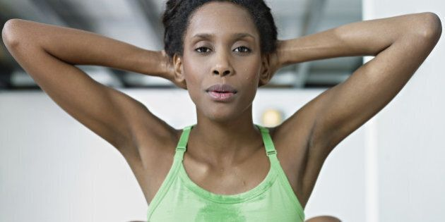 young african american woman in green sportswear exercising abdominals in fitness club, looking at camera....