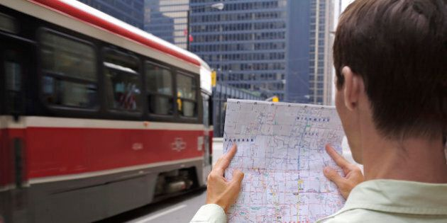 Man holding map standing on city street, Financial District, Toronto, Ontario