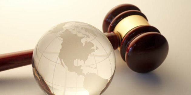 Globe showing North America with gavel signifying justice.