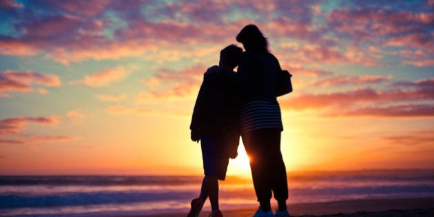 Mother and son silhouetted watching the sunset on a beach.