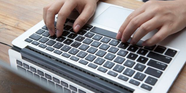 Two hands typing on a keyboard of a laptop