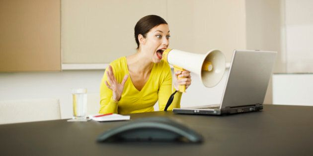 Businesswoman yelling at laptop with bullhorn in conference
