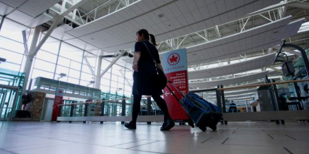 A flight attendant passes in front of the Air Canada check-in counters at Vancouver International Airport...