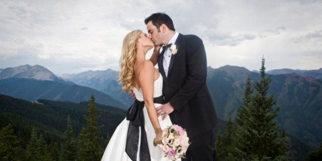 Wedding couple kissing on mountain