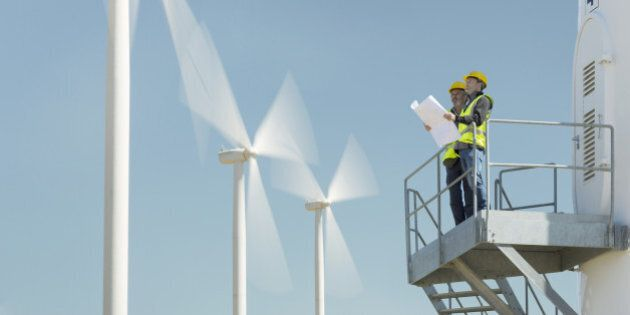 Workers standing on wind turbine in rural