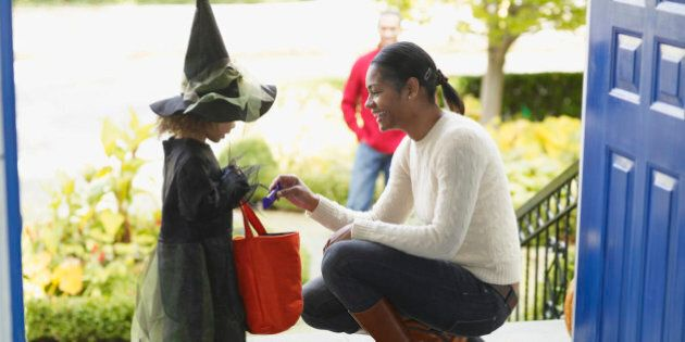African woman giving candy to trick or treater