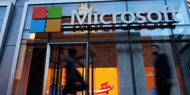 People walk past a Microsoft office in New York on October 6, 2015. Microsoft introduced a pair of big-screen...