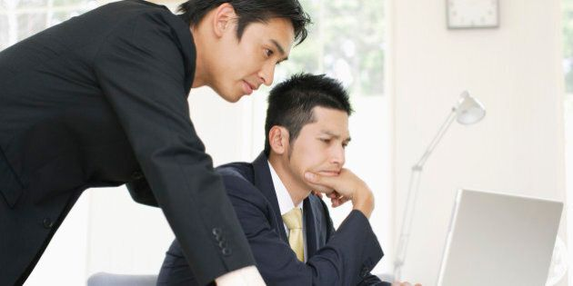 Businessmen looking at laptop PC