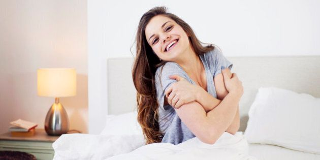 woman giving herself a hug in bed